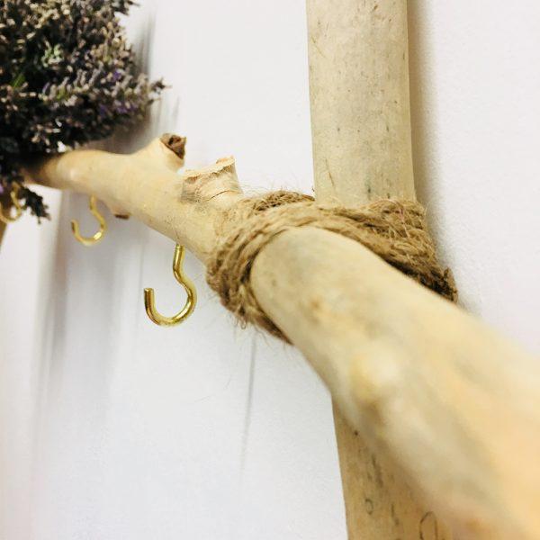 Colgador triangular de madera de mar con flores lavanda.