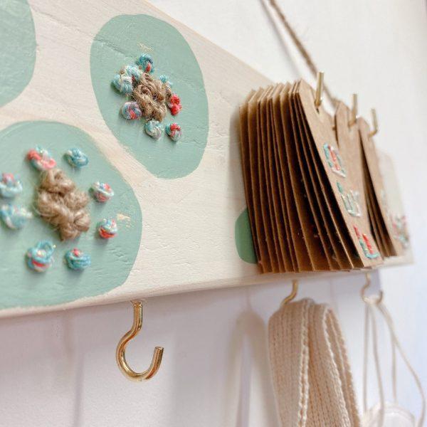 colgador de madera natural bordado con calendario de papel